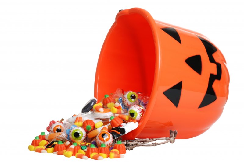 A bucket of candy spilling onto the ground.