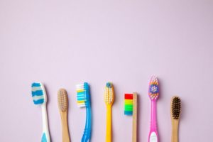 An array of toothbrush styles and colors on a light purple background